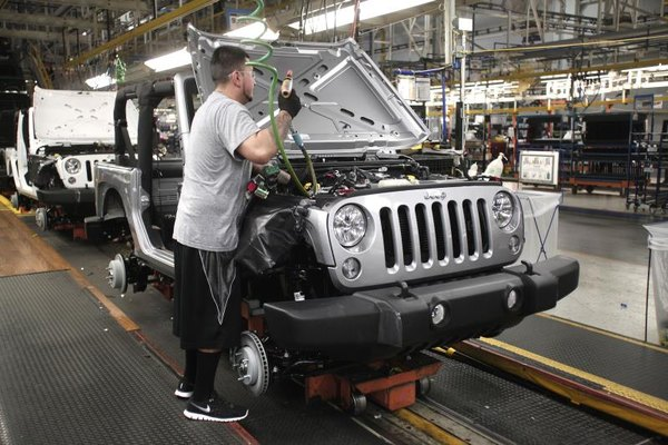 A worker on an assembly line working on a new Jeep Wrangler.