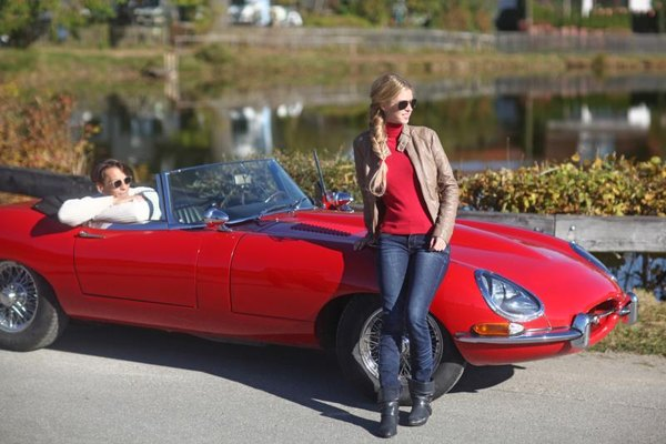 Young couple photographed against their classic car