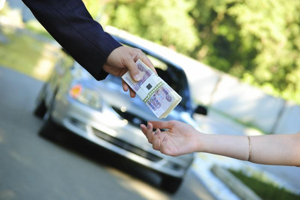 A buyer giving a car seller a bundle of cash in the driveway.