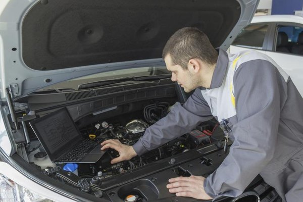 Mechanic performing tests on car with laptop.