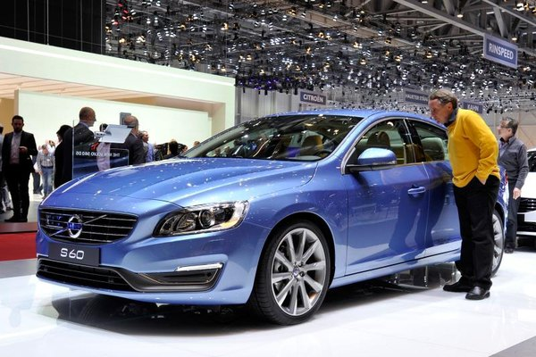 Man inspects a Volvo S60 at the Geneva Auto Show