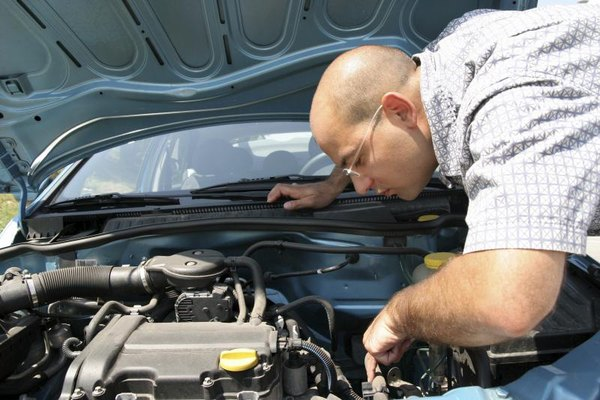 Man looking into car engine