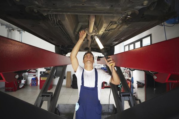 A mechanic inspects the undercarriage of an elevated car