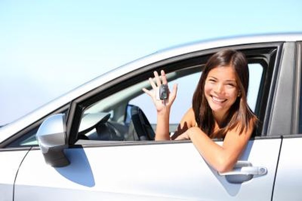 Young woman smiling in a new car.