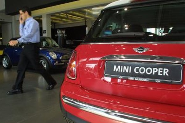 A salesman walks past a Mini Cooper at a car dealership.