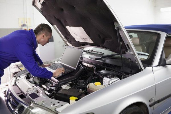 Mechanic with laptop examining the engine of a car.