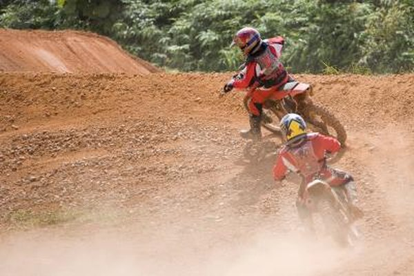 Image of a man and kid riding dirt bikes.