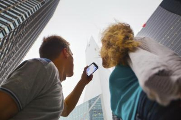 A couple is holding a smartphone up to the sky.