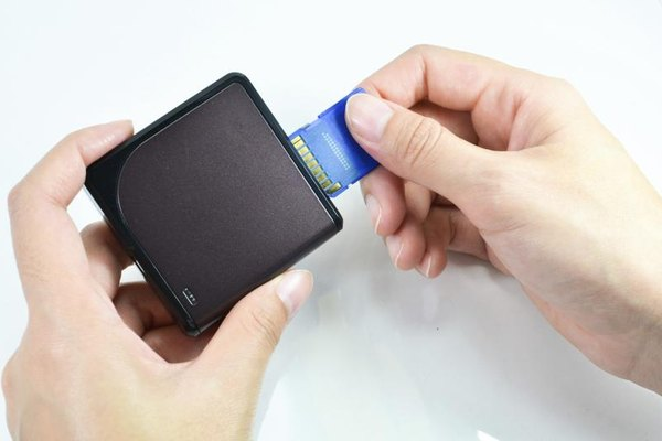 Close-up of hands inserting a SD card into a card reader