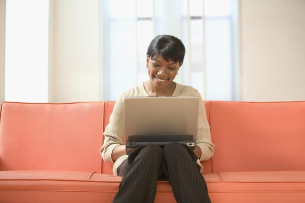 Woman sitting on couch on a laptop computer