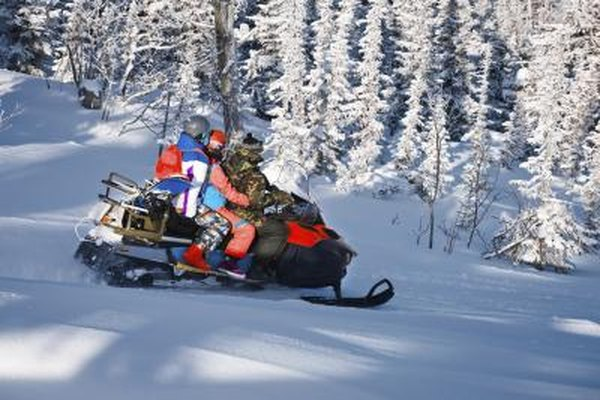 Image of people on a snowmobile in the woods.
