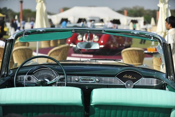 A view from the backseat of a parked 1955 Chevy Bel Air convertible.