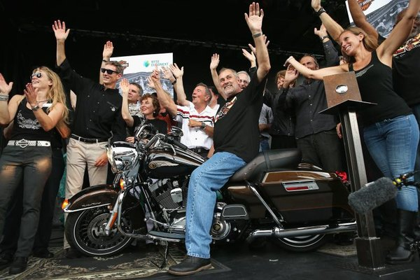 Harley-Davidson Chairman, president and CEO Keith Wandell (seated) celebrates after revving the engine of a 2013 Road King Motorcycle.