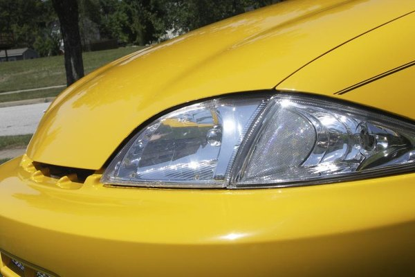 The front end of a yellow car with pinstripes on it.