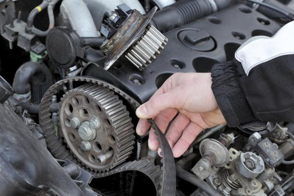 Mechanic changing a timing belt at the camshaft of an engine.