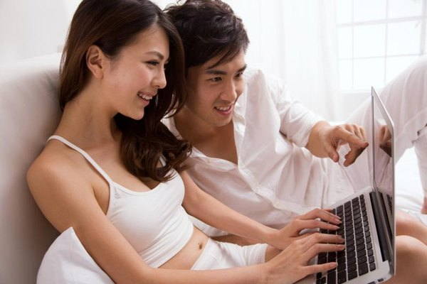 A young couple is using their laptop.