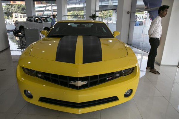 A man stands next to a yellow 2014 Camaro in a dealership showroom