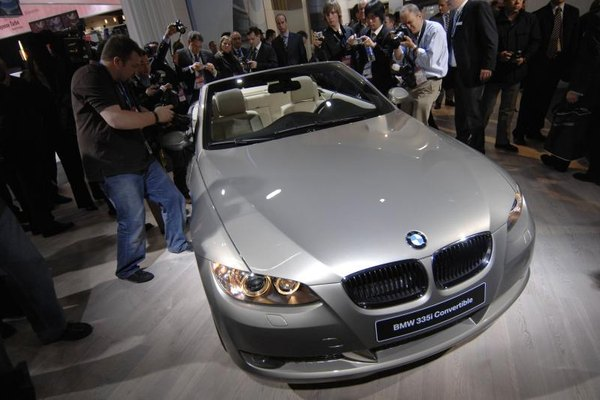 Reporters and photographers crowd around BMW 335i convertible