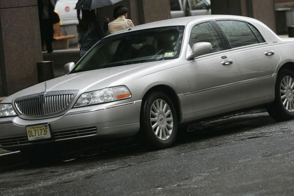 A Lincoln Town Car waiting on the street.