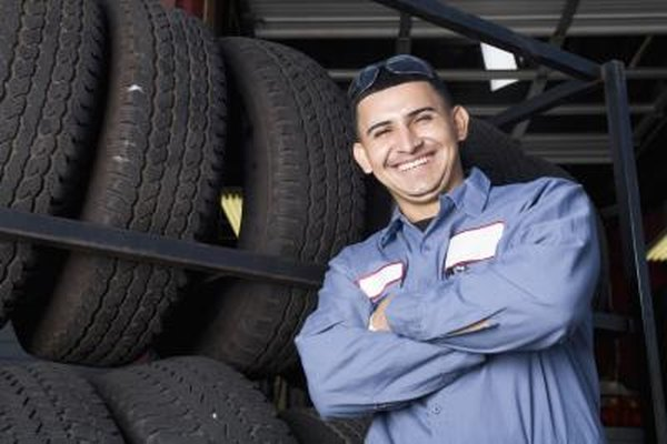 Smiling mechanic standing in front of tires.