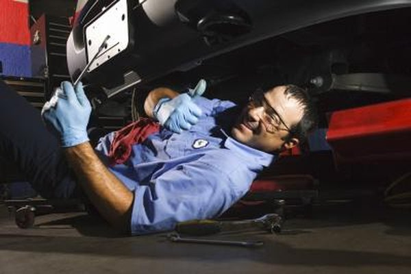A mechanic is working on a car.