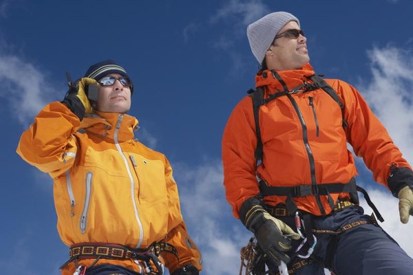 A mountain climber talking on a satellite phone, standing next to his partner