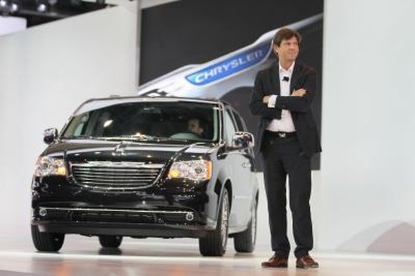 A man standing next to Chrysler's Town and Country minivan at an autoshow.