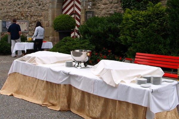 Varias mesas largas y atractivas vestidas con manteles son la base para un buffet de recepción para una boda.