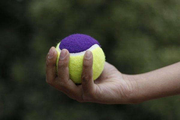 Apretar una pelota de tenis es un ejemplo de un ejercicio para reforzar las manos de los niños.