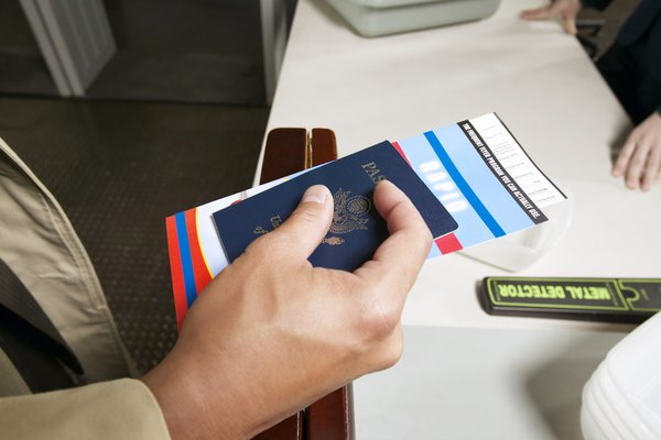 Close Up on a Man's Hand Holding a Passport and Airline Ticket