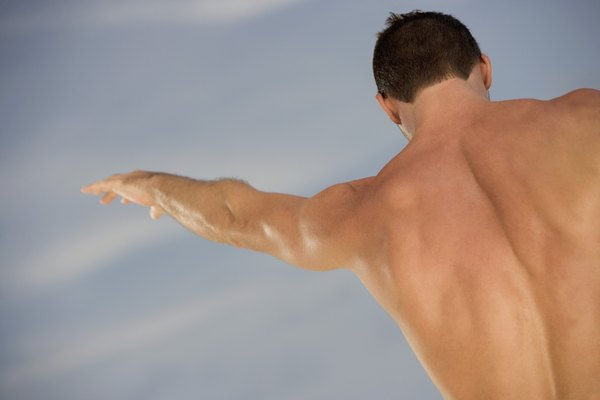 Rear view of a mid adult man with his arms outstretched on the beach