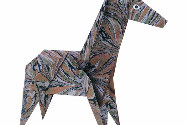 A tu hijo le encantará hacer una jirafa con un cuello largo y una cabeza alta. Comienza al nivel del suelo y pega papel construcción a la pared con cinta adhesiva.