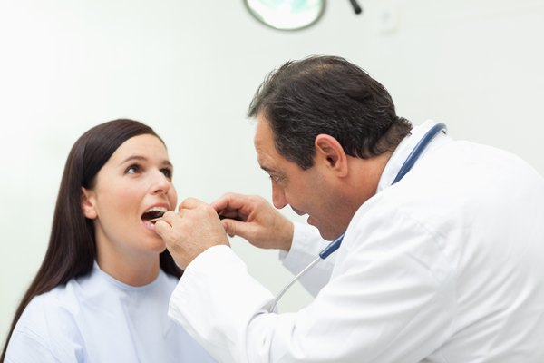 Doctor looking at the mouth of his patient