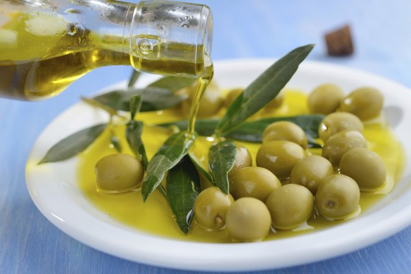 Pouring olive oil into the bowl with green olives