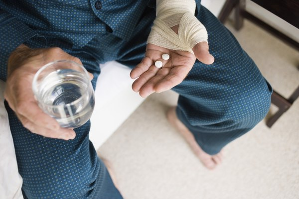 Hands holding pills and water