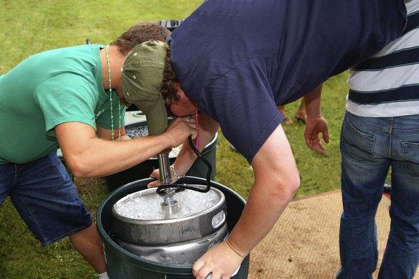 Un hombre tomando de un barril de cerveza parado en sus manos.