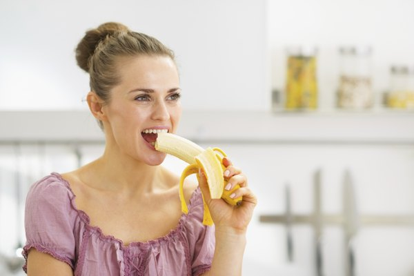 Young woman eating banana in kitchen