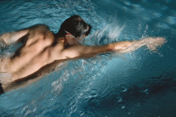 caucasian man swimming in blue water in a swimming pool at a gym or fitness facility