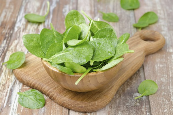 Fresh spinach in a wooden bowl, horizontal