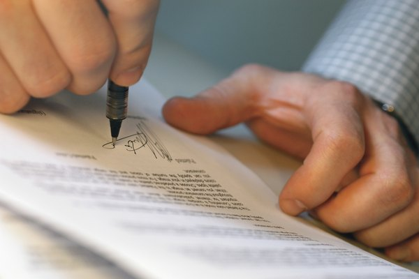Close-up of a mans hands signing on a document
