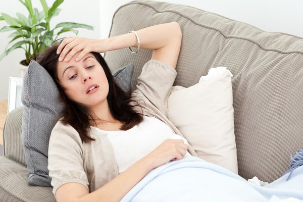 Indisposed woman feeling her temperature