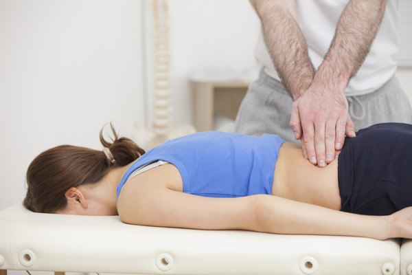 Chiropractor touching the back of woman while standing