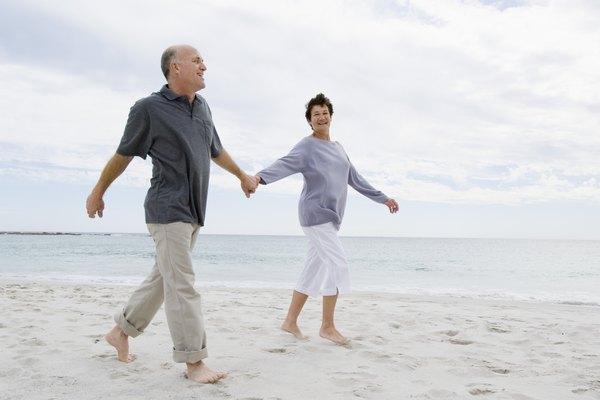 Mature couple holding hands on beach