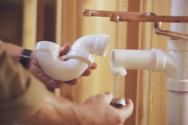 Los fontaneros usan cemento para soldar tubos plásticos de PVC para una unión permanente.