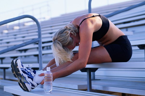 Woman seated on bleachers, stretching