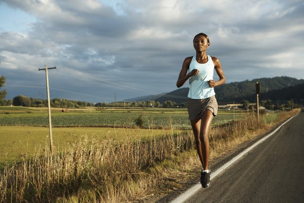 Young woman jogging by road in rural landscape