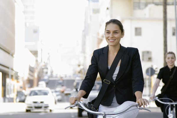 Smiling businesswoman riding bicycle along city street