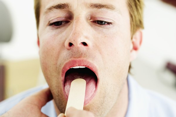Young man getting his throat checked with a tongue depressor