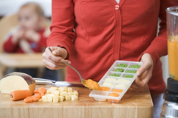 Woman filling tray with baby food