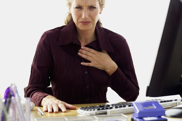 portrait of a businesswoman sitting in front of a computer with her hand on her chest